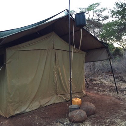 The back of the tent, where the bucket is filled with water for showering